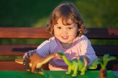 Toddler kid playing with a toy dinosaur. Toddler kid, little girl having fun playing with a toy dinosaur, horizontal natural light photo royalty free stock photo