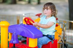 Little girl at the amusement park, riding toy train. Royalty Free Stock Photography