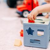 Toddler kid solves sorter puzzle block at home. Toddler boy solves sorter puzzleToddler boy finds block with matching hole shape playing in child room royalty free stock photos