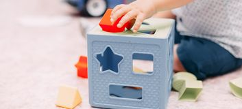 Toddler kid solves sorter puzzle block at home. Toddler boy solves sorter puzzleToddler boy finds block with matching hole shape playing in child room stock photos