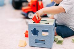 Toddler kid solves sorter puzzle block at home. Toddler boy solves sorter puzzleToddler boy finds block with matching hole shape playing in child room royalty free stock images