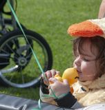 Toddler Kisses her Rubber Duck for Good Luck before the races begin. A child dressed in a rubber ducky costume kisses her entry at the 16th Rubber Ducky Festival stock photography