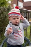 Toddler in knitted bobble hat Stock Photo
