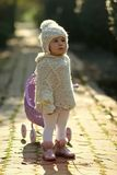 Toddler in knitted clothes playing outdoors. Role play games concept. Child and childhood lifestyle. Girl walking with vintage doll stroller on sunny day. Baby royalty free stock photography