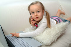Toddler with laptop and phone Stock Image