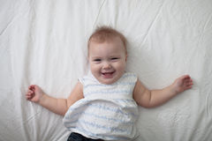 Toddler laugh baby on bed, first teeth Royalty Free Stock Photos