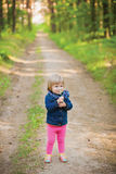 Toddler laughing girl in forest with flowers. Cute little girl walking at forest smelling lily flowers smiling happily Stock Images