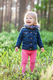 Toddler laughing girl in forest. Toddler laughing stylish girl in forest with sun backlight Stock Image