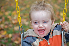 Toddler laughing in a swing. Royalty Free Stock Image