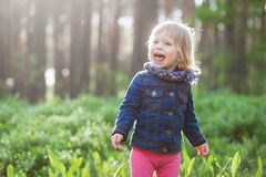 Toddler laughing stylish girl in forest. With sun backlight Royalty Free Stock Images