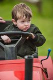 Toddler on lawnmower. A young boy sitting on a ride-on lawnmower stock photo