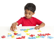 Toddler learning to spell with alphabets. Isolated, white royalty free stock photos