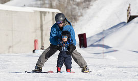 Toddler Learns to Ski with Dad. Safely Dressed Stock Image