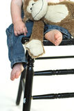 Toddler Legs. Image of a toddler sitting on a black chair, holding a stuffed monkey, only his lower body visible Royalty Free Stock Images