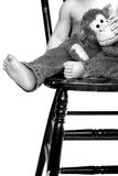 Toddler Legs. Black and white image of a toddler sitting on a chair, holding a stuffed monkey, only his lower body visible Stock Photography
