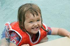 Toddler with life jacket. Sweet toddler hanging on the edge of a swimming pool and wearing a life jacket Stock Photography