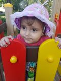 Toddler life in north europe. Cute toddler with pink summer hat in kindergarden playground peeking from colorful yard attraction Royalty Free Stock Photos