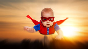 Toddler little baby superman superhero with a red cape flying th. Rough the sky stock images