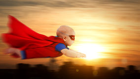Toddler little baby superman superhero with red cape flying thro. Toddler little baby superman superhero with a red cape flying through sunset sky above the city royalty free stock photos