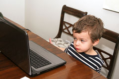 Toddler looking at computer. Toddler with striped shirt looking at computer Stock Image