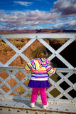 Toddler Looking Over the Edge of a Bridge. A young, toddler girl peers over the edge of Navajo Bridge at Marble Canyon, Arizona. She is looking down towards the Royalty Free Stock Photography