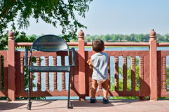 Toddler looking at river. Rear view of male baby or toddler looking at picturesque river over fence Stock Photography