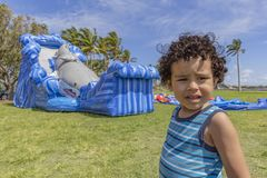 A toddler looks at the camera with a confused look while the bounce house inflates royalty free stock images