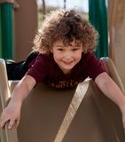 Childs play. A Caucasian child with curly blond hair,  looks directly into your eyes just before coming down a slide Royalty Free Stock Image