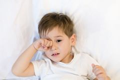 Toddler is lying in bed ready to sleep. Asian boy 3 years going to sleep at home. sleepy eyes stock image