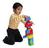 Toddler Making a tall Building with Blocks Royalty Free Stock Image