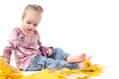 Toddler with maple leaves Stock Images