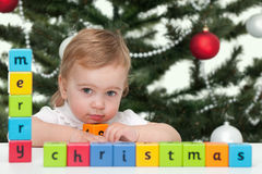 Toddler at a merry christmas tree. A pretty girl with a sign merry christmas on the blocks is standing at a new year tree Royalty Free Stock Images