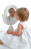 Toddler in Mirror. Toddler girl sitting on floor, in front of wicker mirror, smiling, in white dress, on white background Royalty Free Stock Photo