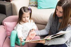 Toddler And Mom Going Through Picture Book. High angle view of preschool girl and mother looking at book at home royalty free stock photography