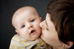 Toddler and mum. The mother is holding a three-month son and kisses his cheek Royalty Free Stock Photos