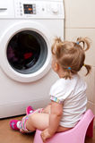 Toddler near clothes dryer. Young girl, toddler sitting in front of a clothes or laundry dryer royalty free stock photo