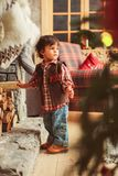 Toddler near fireplace. Small boy in casual clothes near fireplace with wood, Scandinavian house interior stock photography