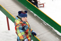 Toddler near slide. Toddler is near slide at playground in winter Stock Image