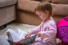 Toddler Opening up Christmas Presents. A girl toddler opening up presents on Christmas morning Royalty Free Stock Images