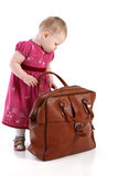Toddler opens an old travel bag Royalty Free Stock Photos