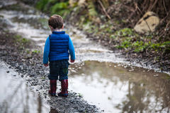 Toddler outdoors beside large puddle. Small boy in Wellington boots wearing a blue quilted body warmer standing on gravel path beside large puddle stock image