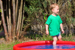 Toddler in the paddling pool Stock Image