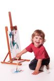 Toddler painter. Studio portrait of a two year old girl painting on an easel with a paint brush and palette. Isolated on a white background royalty free stock photos