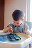 Toddler painting with watercolors. Little boy painting with colorful paints Stock Photo