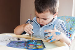 Toddler painting with watercolors. Little boy painting with colorful paints Stock Image