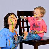 Toddler paints her grandmother's face. Royalty Free Stock Image