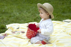 Toddler palying in the garden with a red bucket Stock Photography
