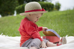 Toddler palying outdoors with memo cards Royalty Free Stock Photo