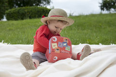 Toddler palying outdoors with memo cards Royalty Free Stock Image