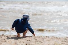 Toddler in panama and jacket at beach royalty free stock photos